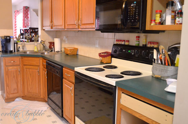 Kitchen cabinets before painting. Builder-grade cabinets in need of a facelift. How to paint builder grade cabinets white.