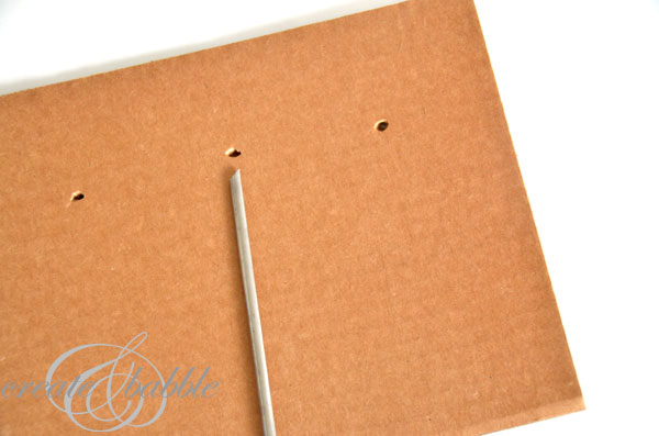 Poke holes in cardboard and then attach the hardware. Carry outside to spray paint.