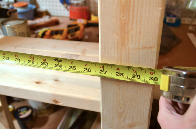 measuring-width-of-paint-storage-shelf-built-with-2x4s