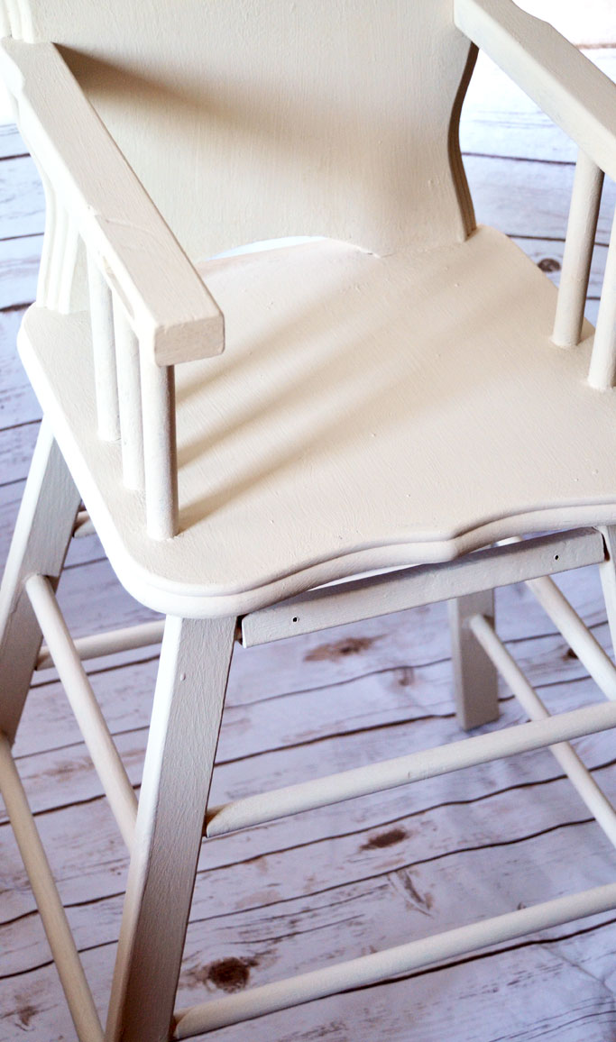 Old high chair restoration started with two coats of Amy Howard at Home One Step Paint in Linen