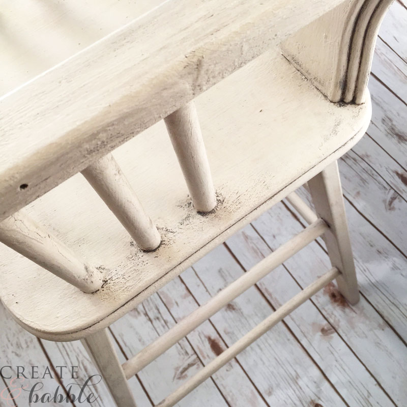 Lifting off milk paint from restored high chair gives the toscana finish