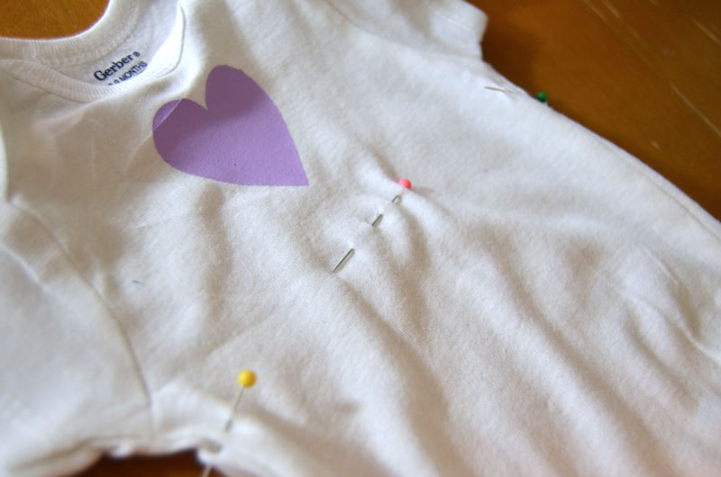 Use pins to mark placement of skirt of onesie dress