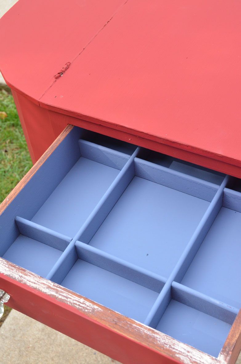 sewing cabinet painted red on the outside and blue on the inside of the drawers