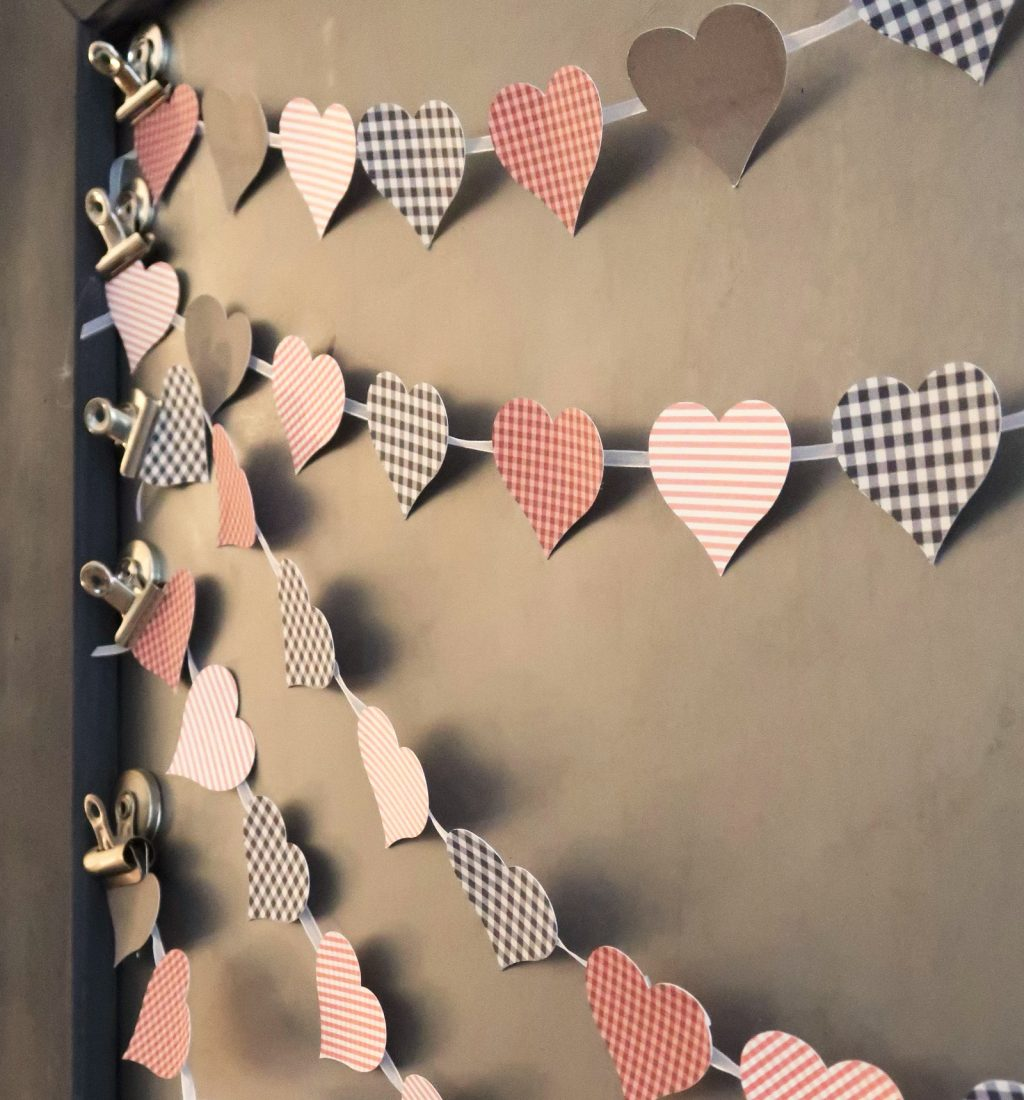 Print Then Cut Patterned Paper Heart Banner made with Cricut hanging on picture frame